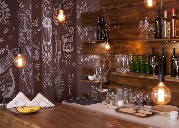 Empty cafe bar interior design with artistic drawing in the back. Wine bottles . Light bulbs hanging from the ceiling.